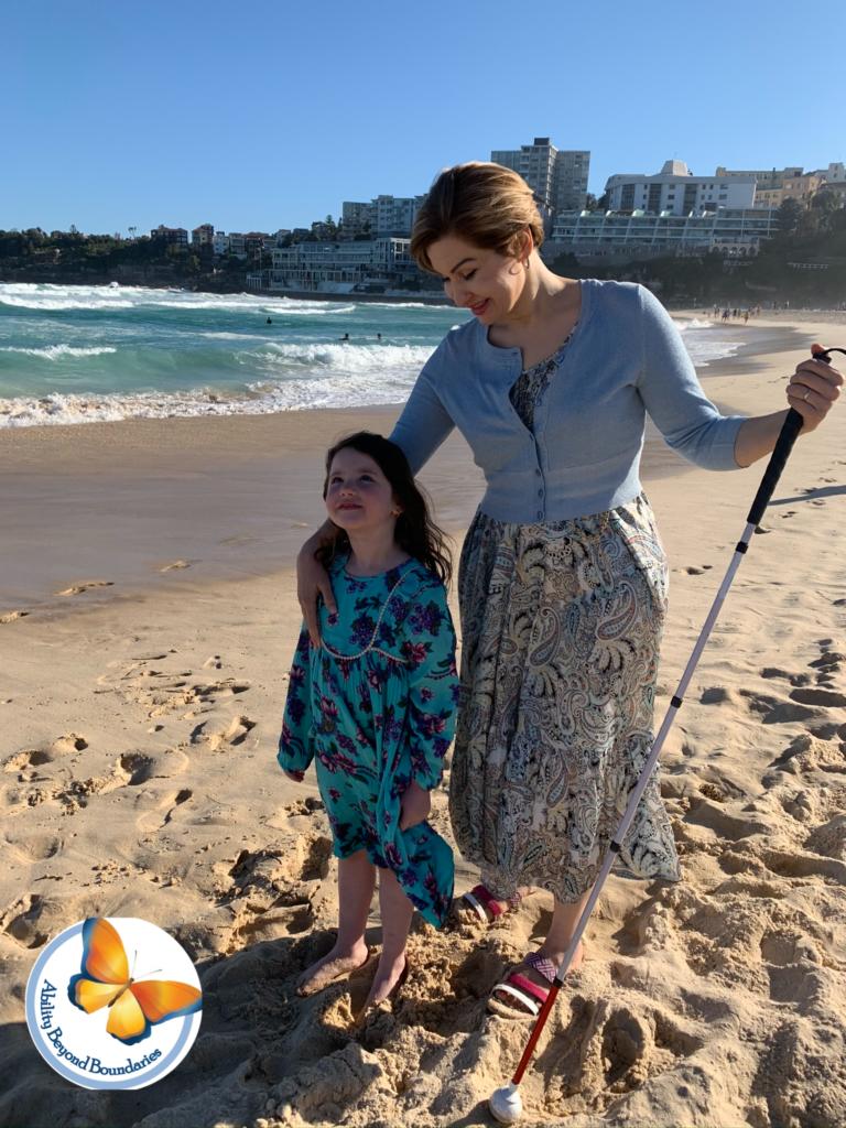 تصویر زنی در کنار دریا با عصای سفید در کنار یک دختر بچه