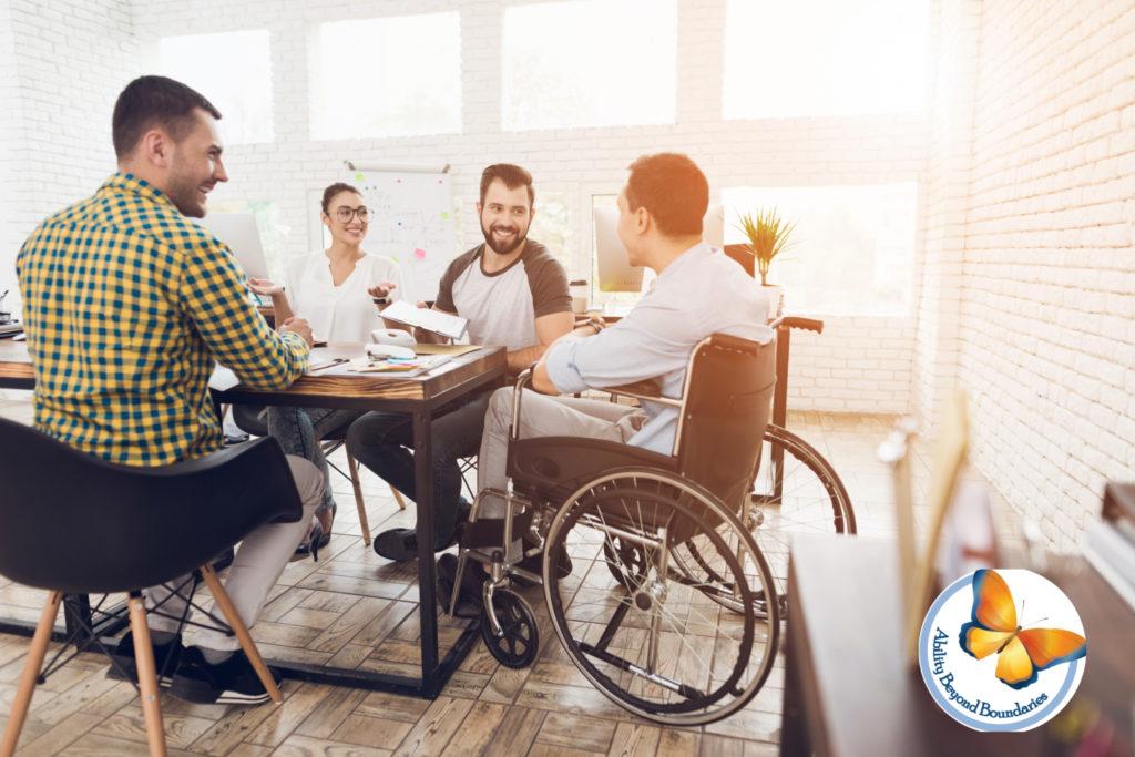 مردی روی صندلی چرخدار با لبخند به همکاران خود خوشامد می گوید