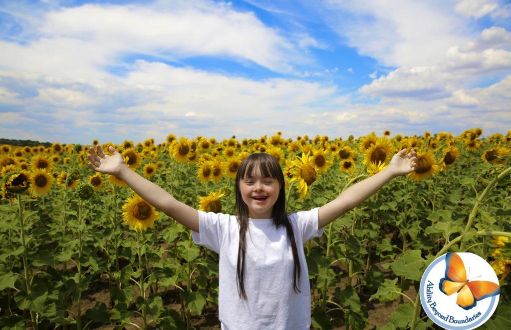 دختر دارای سندروم داون در میان مزرعه گل آفتابگردان دستهایش را بالا برده و لبخند می زند.