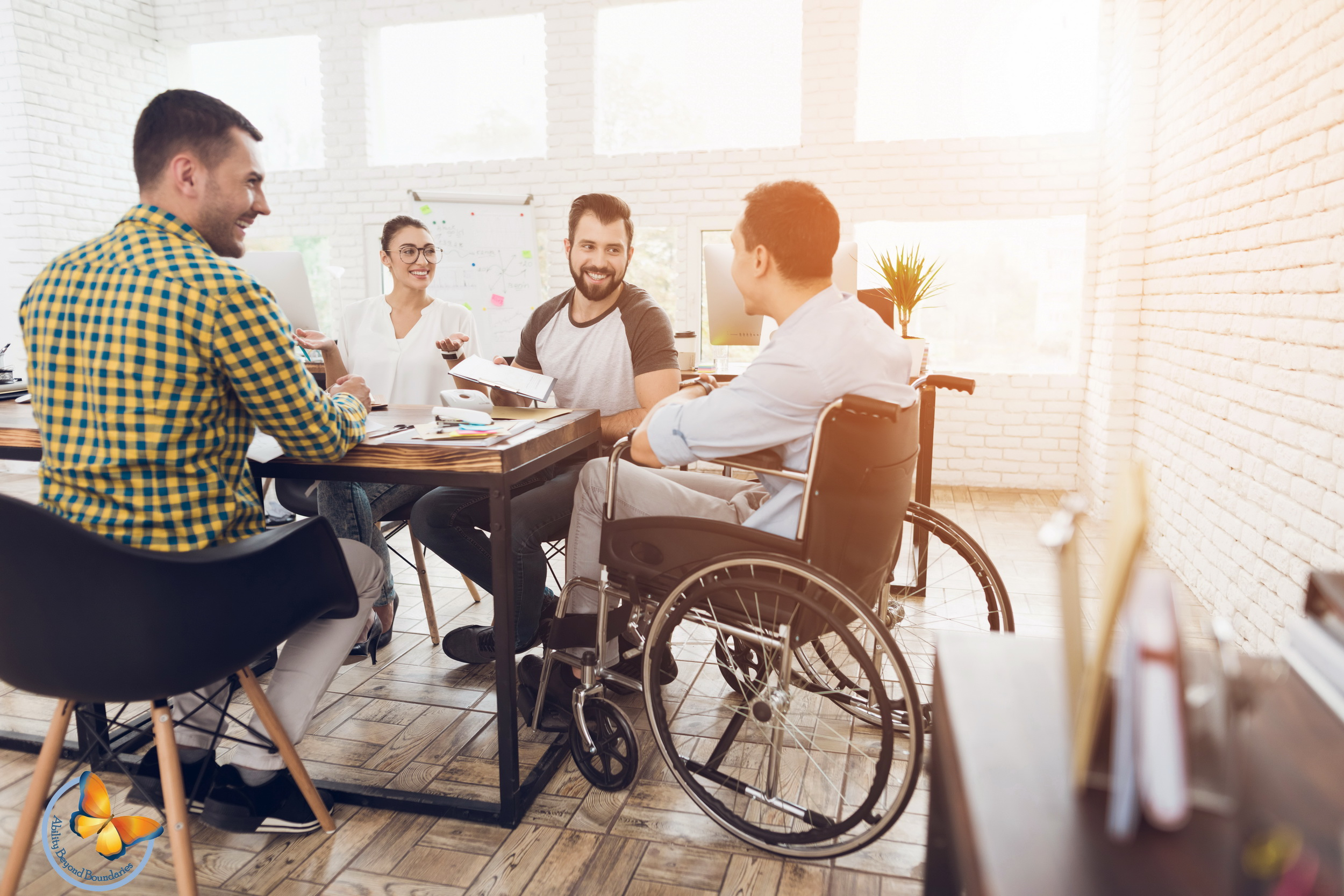 A smiling man sitting in a Wheelchair welcomes his colleagues in a meeting