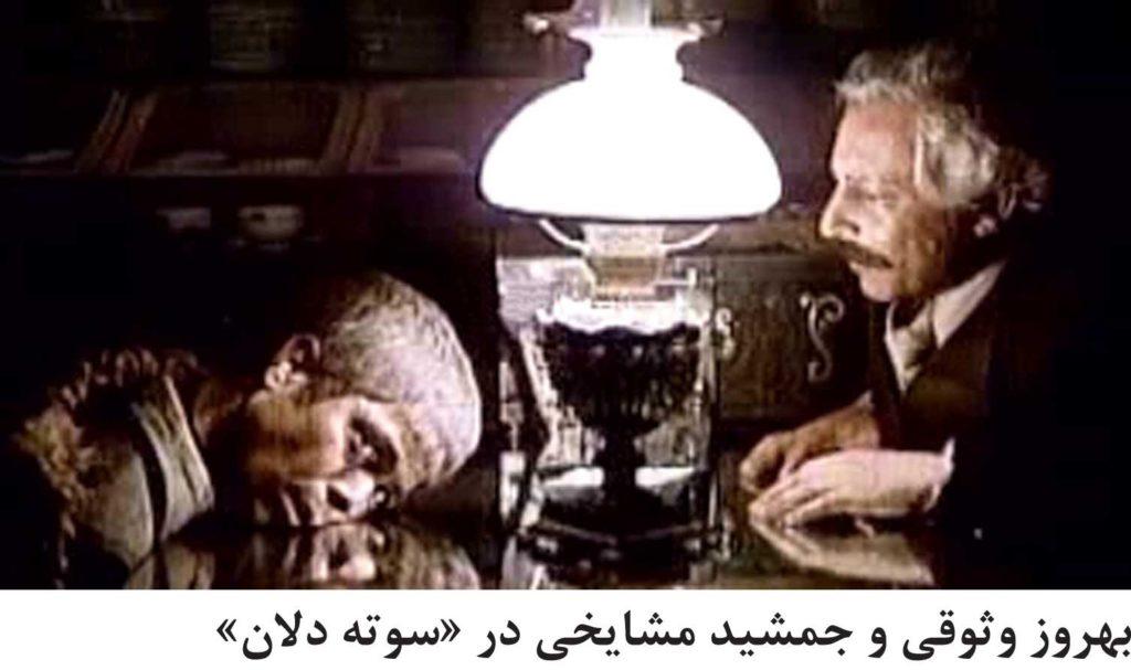 """تصویر جمشید مشایخی و بهروز وثوقی (با معلولیت ذهنی) در فیلم """"سوته دلان"""": در دو طرف میز روبروی هم نشسته اند و بهروز با غم سمت چپ صورتش را روی میز گذاشته چراغ گردسوز قدیمی بزرگی روی میز روشن است"""