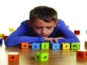 پسر بچه ای با مکعبهای رنگی با حروف اوتیسم در مقابلش