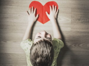 پسربچه ای قلب کاغذی قرمز رنگی را با دو دست نگهداشته است