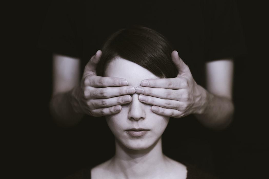 دو دست در یک اتاق تاریک از پشت چشمان زنی را گرفته است