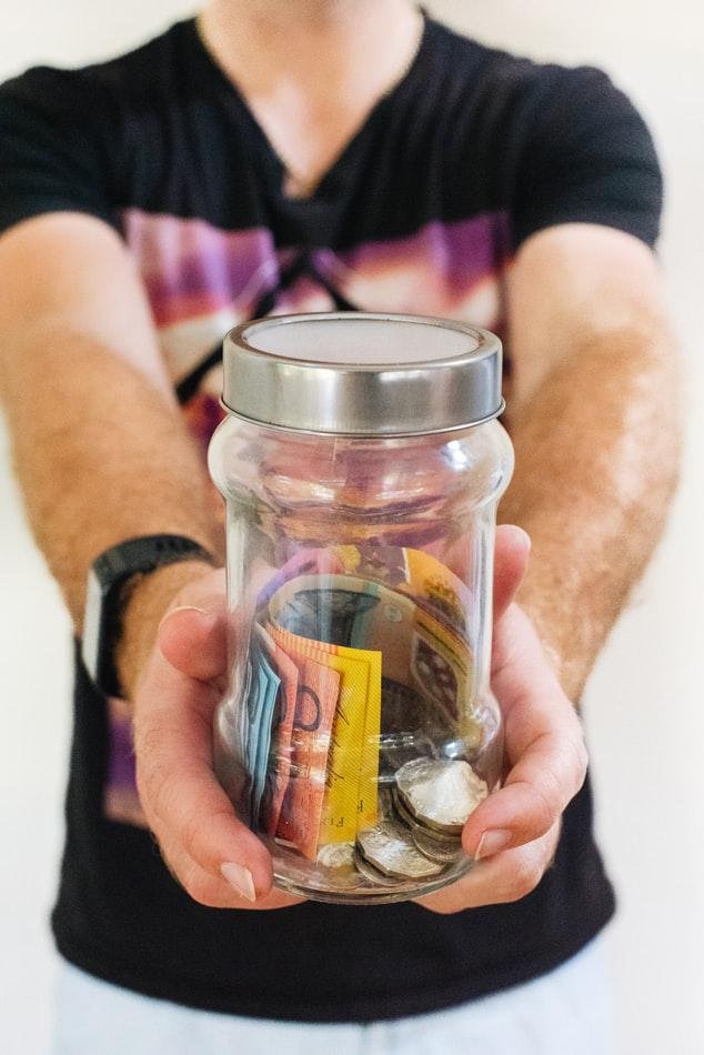 دو دست شیشهی پول پس انداز را به سمت بیننده گرفته است
