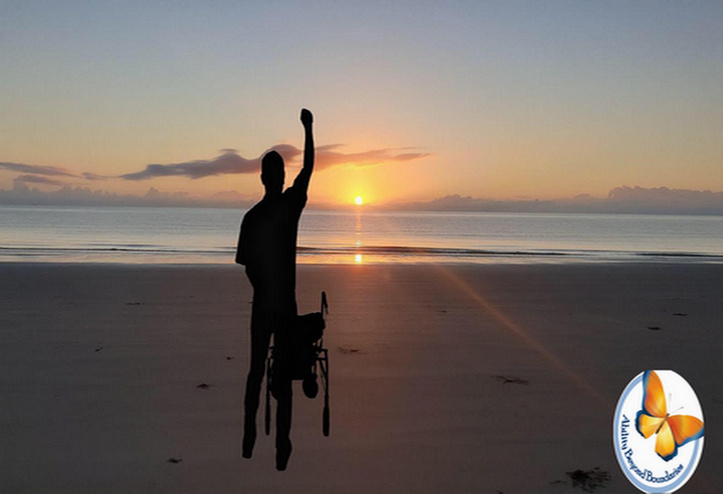 Sunrise near the ocean with a man standing with his walker while he has his right hand raised powerfully