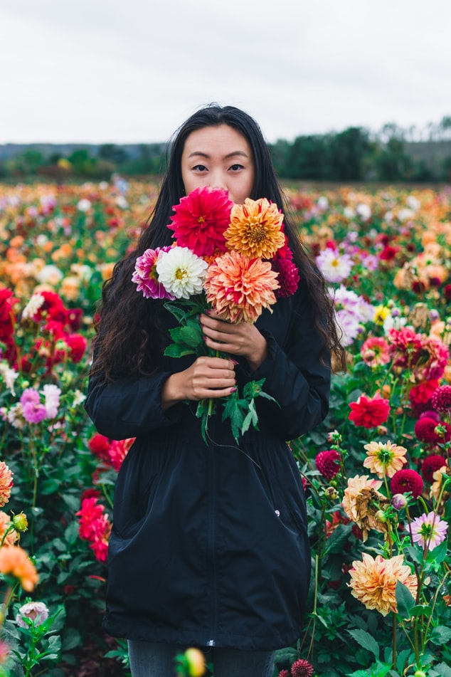 A young woman has a bouquet of flowers covering her mouth