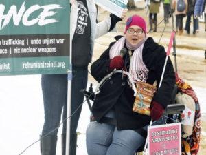 """زنی بر روی صندلی چرخداربا پلاکاردی در دست. روی پلاکارد نوشته است: """"نه در پاسخ به دکترها برای سقط جنین"""""""